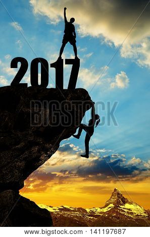 Hiker climbs into the New Year 2017 at sunset.