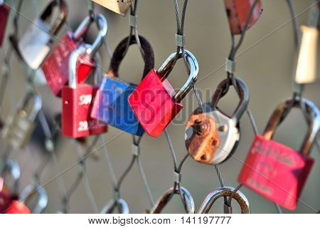 Multicolored padlocks on a fence, love symbols