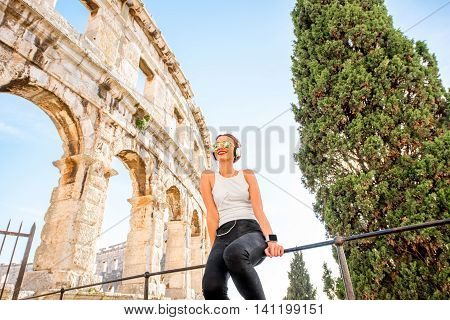 Young sports woman resting after the training near the ancient coliseum in Pula city
