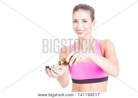 Young Female At Gym Spilling Bottle Of Pills
