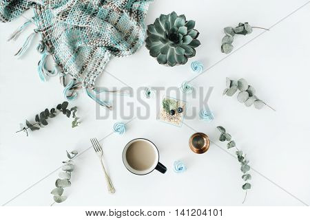 Breakfast composition with coffee with milk blue cakes succulent fork eucalyptus plaid on with background. Flat lay top view