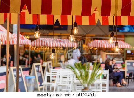 blurred background cafe with Edison lamps and red striped canopy