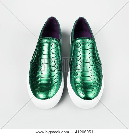 pair of new green shoes in grey background
