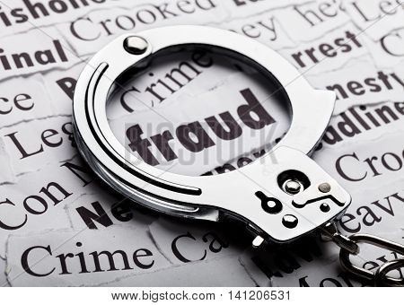 Handcuffs frame the word fraud among newspaper cuttings