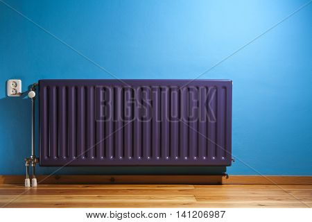Purple central heating radiator and a blue wall with power point in the Netherlands