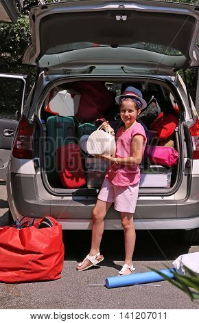 Little Girl With Hat Loads The Trunk