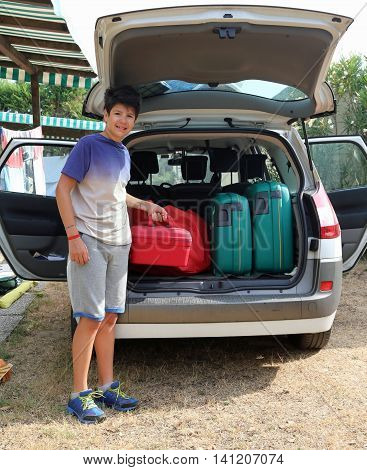 Boy Helps Load The Trunk Before Leaving For A Long Journey