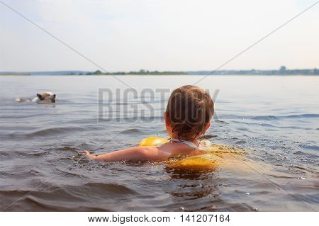 child and dog together swimming in the water. kid and dog swimming towards each other. the concept of devotion of a pet