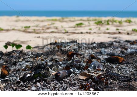 Burnt glass garbages at the beautiful beach