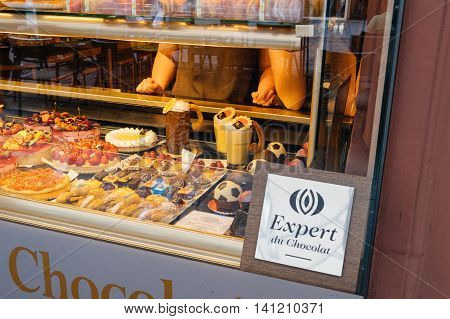 PARIS FRANCE - CIRCA 2016: Expert du Chocolat - Chocolate expert certificate sign in front of chocolate candy store in the city of Paris with owners disputing behind the glass