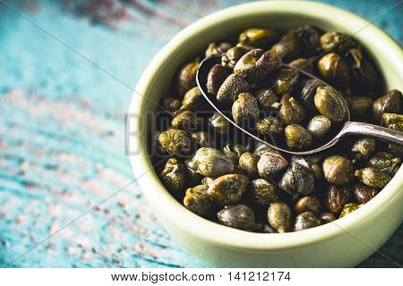 Capers in the bowl on the light blue background