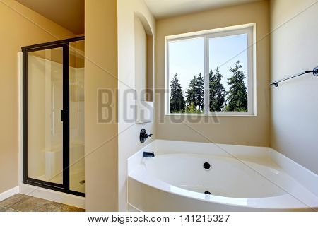 Beige Bathroom Interior With White Bath Tub And Glass Shower