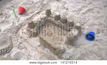 A sandcastle made in a sand pit with plastic childrens toys