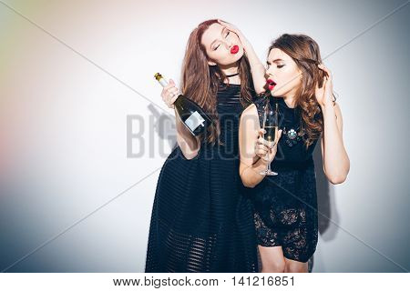 Two beautiful women in night dress  posing with champagne isolated on a white background