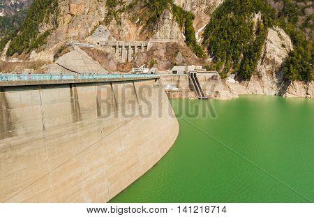 Dam Between Mountains With Green Lake At Kurobe Dam  Japan