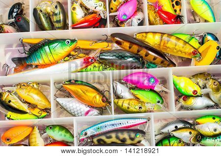 Colorful fishing lures and accessories in the box background