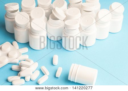 Many pills and tablets isolated on light blue background. Pharmaceutical medicament cure in container for health. Antibiotic painkiller closeup. Copy space for text.