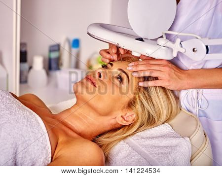Woman middle-aged in spa salon with young beautician. Tweezing eyebrow by beautician. Woman beauty and healthy.
