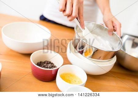 Woman sieved the flour to bake cookies