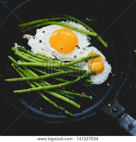 Fried eggs with asparagus in iron cast skillet, close up. Square composition, toned image