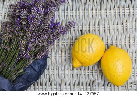Bouquet of purple fresh fragrant lavender wrapped in blue paper with two fresh yellow lemons on wicker wooden background