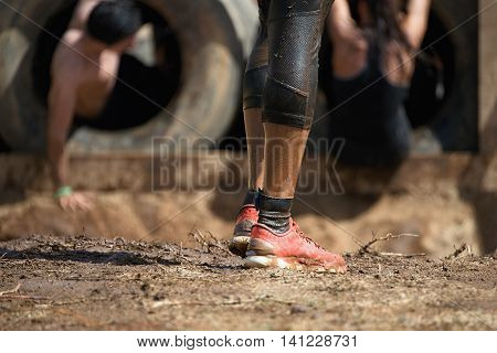 Mud race runners,detail of the legs,in the background obstruction tires