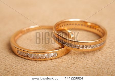 Two beautiful golden wedding rings with brilliants close up. Marriage concept