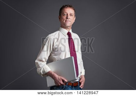A confident middle age man smiling with a laptop