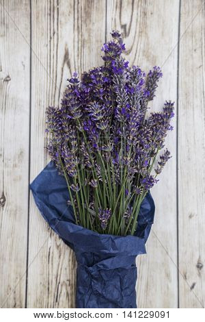 Bouquet of purple fresh fragrant lavender wrapped in blue paper on wooden background