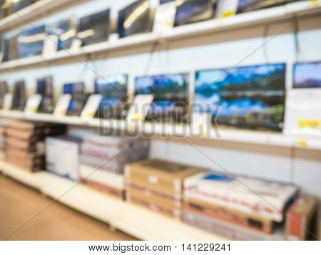 Blurred eletronic department store with television shelf. Blurred background with bokeh