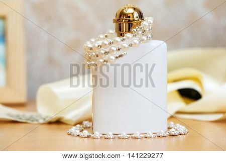 White bottle of wedding parfume with costume jewelry