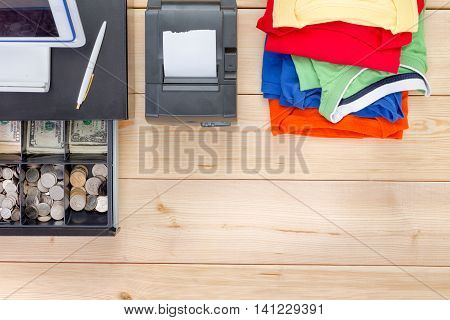 Neatly folded pile of brightly colored summer clothes an adding machine and open cash register with American dollar currency on a wooden table in an overhead view with copy space conceptual of sales