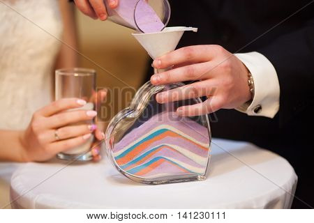 Sand ceremony on wedding glass vase for bride and groom. Marriage concept