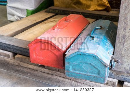 Grunge Red And Blue Metal Tool Boxes On Wood Palette In Factory