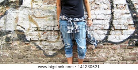 Cropped portrait of stylish person in casual clothes: black t-shirt, plaid shirt  and ripped jeans standing against colorful urban city brick wall background.