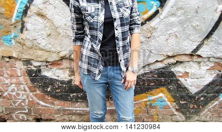 Cropped portrait of stylish young man woman in black t-shirt, plaid shirt and ripped jeans standing against colorful urban city brick wall background.