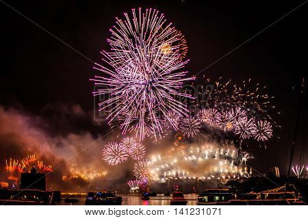 Fireworks with boats parade at Harbour Bridge in Sydney bay at midnight for the new years eve 2015, shot from a boat.