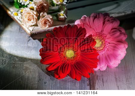 Still life with gerbera roses and daisies in front of a picture frame on a wooden table