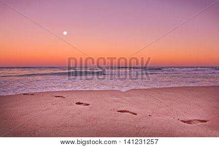 Empty sandy beach with footprints ocean waves and full moon in expressive dusk orange and purple light in Mallorca Balearic islands Spain.