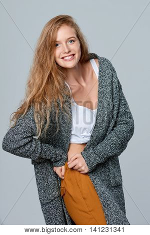 Happy laughing beautiful woman in warm knitted cardigan, over gray background
