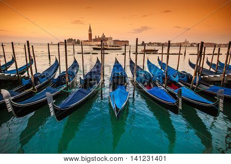 Gondolas moored by Saint Mark square - Venice during sunrise, Italy, Europe.
