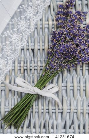 Bouquet of purple fresh fragrant lavender tied with white textile ribbon and white handmade lace fabric on wicker wooden background