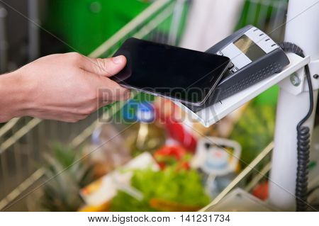 Customer paying with NFC technology in grosery store