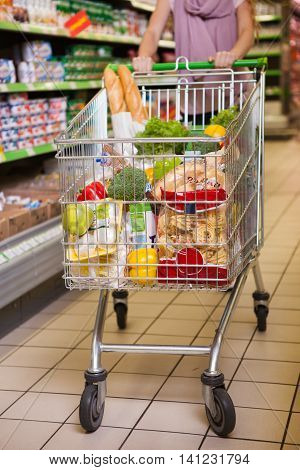 Woman shopping with her trolley full of products in supermarket