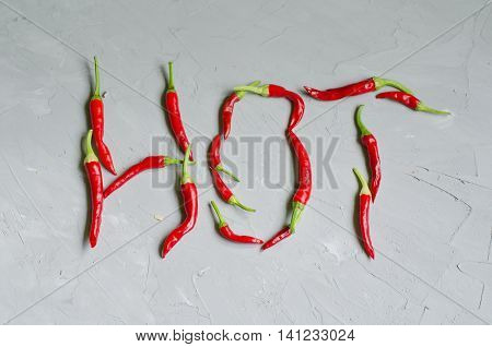 Word Hot written with little chilly peppers on gray background