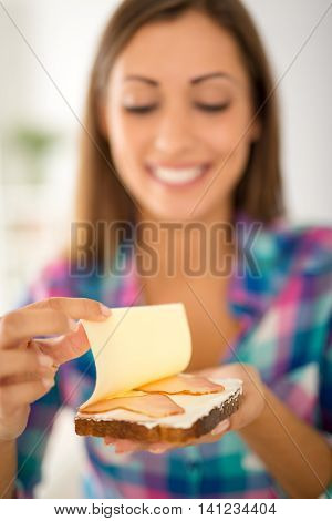 Close-up of a female hands makin fresh sandwich. Selective focus. Focus on foreground on sandwich.
