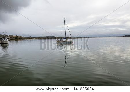 Sailboat in the fog, Port of St Helens, Georges Bay, Tasmania, Australia. St Helens is the most important city of the northeast coast and is famous for the Bay of Fires.