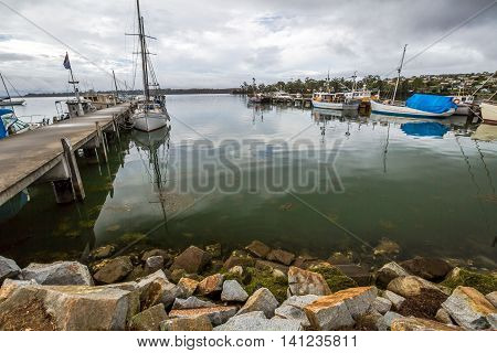 Fishing Boats docked at jetty in St Helens harbor, Georges Bay, Tasmania, Australia. St Helens is the most important city of the northeast coast and is famous for the Bay of Fires