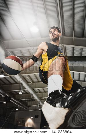 Full length portrait of a basketball player with a ball against gray gym background