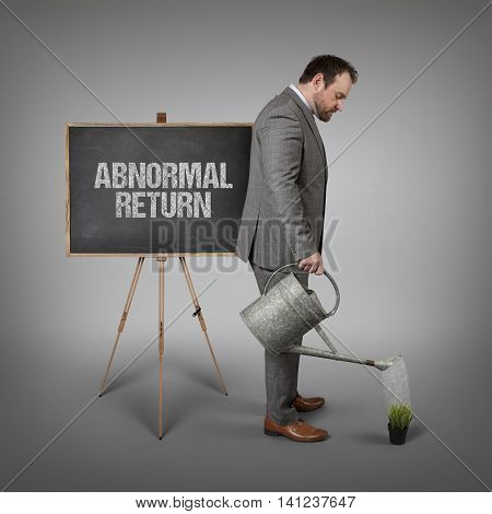 Abnormal return text on  blackboard with businessman watering plant